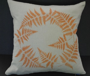 Hand stenciled ring of copper colored fern leaves on a dark natural linen square pillow by 2 faced linen