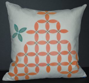 Terra cotta and blue petal design on a square white linen pillow
