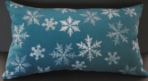 Hand stenciled white snowflakes on a turquoise linen lumbar pillow by 2 faced linen
