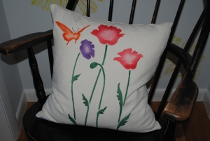 Hand stenciled California poppies and a butterfly on a linen square pillow