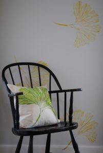 Hand stenciled green ginkgo on a white linen square pillow rests in a black bentwood chair by 2 faced linen