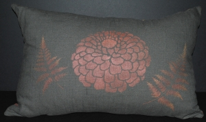 Hand stenciled rose gold zinnia and fern leaves on a charcoal linen lumbar pillow by 2 faced linen
