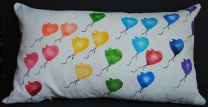 Hand stenciled rainbow of balloons on a white linen lumbar pillow by 2 faced linen
