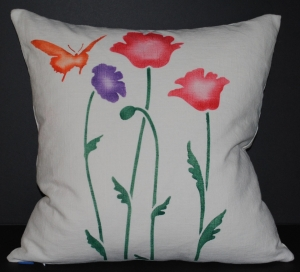 Hand stenciled California poppies and a butterfly on a square linen pillow