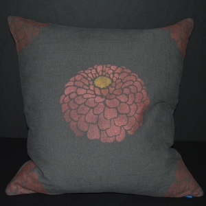 Hand stenciled rose gold zinnia on a charcoal linen square pillow