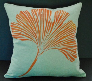 Hand stenciled orange ginkgo leaf on a sage grey linen square pillow by 2 faced linen