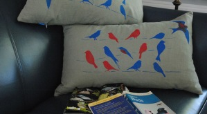 Hand stenciled colorful birds on a sage grey linen lumbar pillow by 2 faced linen